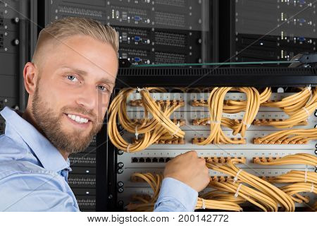 Portrait Of A Smiling Young Computer Technician Checking The Server Cables In Data Center