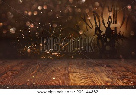 Abstract bokeh background with fireworks and a clock in front of a wooden table for a solemn decoration