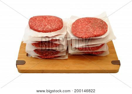 Raw Beef Burgers Stacked on a Wooden Cutting Board