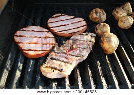 Grilling a Lamb Chop Ham Steaks and Whole Potatoes