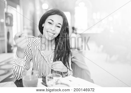 Young brunette woman with long hair looking camera and smiling while eating chocolate cake in coffee shop.