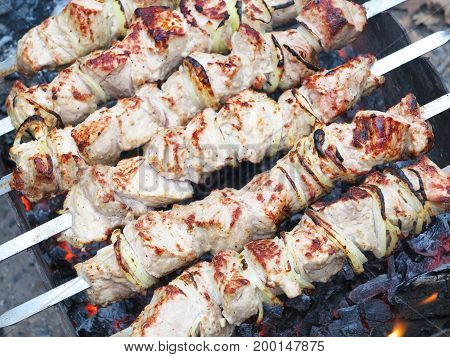 Grilled kebab cooking on metal skewer. Roasted meat cooked at barbecue.Traditional eastern dish shish kebab. Grill on charcoal and flame picnic street food