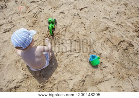 Baby boy playing on sand at the beach with toy backhoe and watering can. El Rompido Huelva Spain