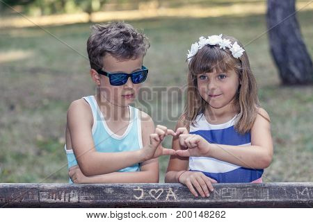 Little Sweet Boy And A Girl Standing By The Bench In The Park And Having Fun