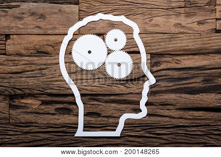 Directly above shot of paper businessman's head outline with metallic gears on wooden table