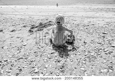 baby boy playing with sand at the beach. El Rompido Cartaya Huelva Spain