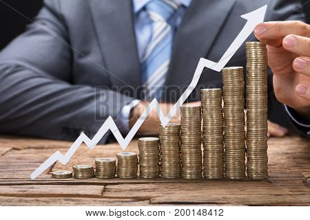 Midsection of businessman holding paper arrow on stacked coins arranged in increasing order on table