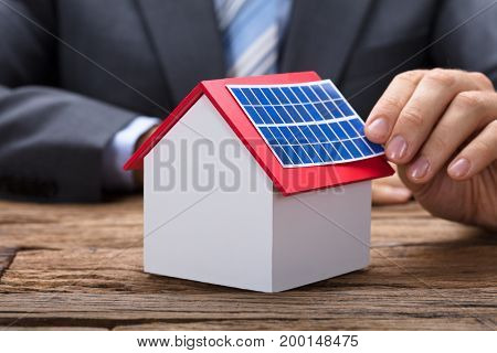 Midsection of businessman sticking solar panel on model home at wooden table