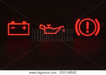 Macro of error signs in car. Red icons of battery, oil and hand break