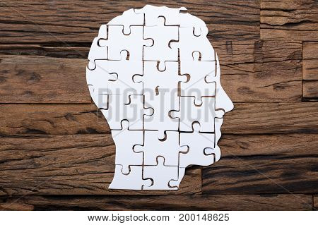 Directly above shot of businessman's head made from paper jigsaw puzzle pieces on wooden table