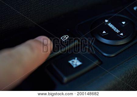 Lock car doors theme. Finger push lock button of car doors