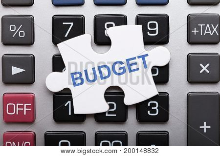 Directly above shot of jigsaw puzzle piece with budget text on calculator