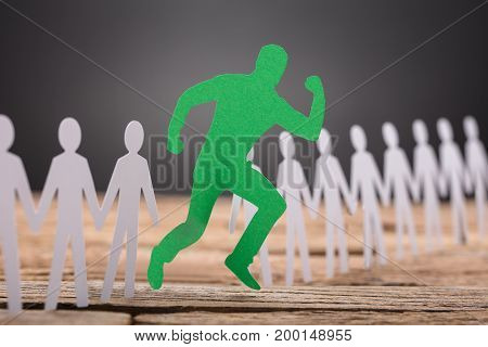 Green paperman running against paper team on wooden table against black background