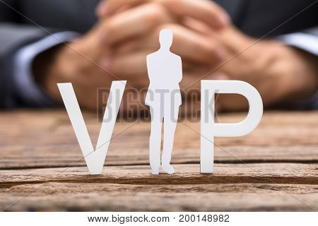 Cropped image of businessman and VIP text on wooden table
