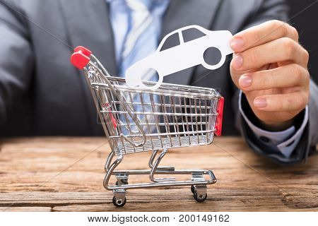 Midsection of businessman holding paper car over shopping cart on wooden table
