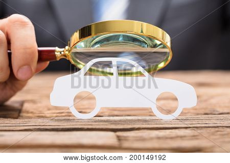 Cropped image of businessman's hand examining paper car with magnifying glass at wooden table