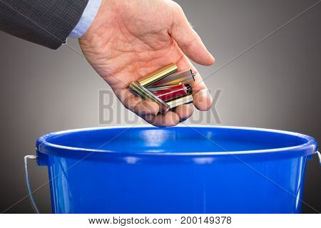 Cropped hand of businessman throwing old batteries in blue bucket against gray background