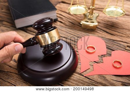 Judge hitting mallet by broken paper heart with rings and justice scale on wooden table