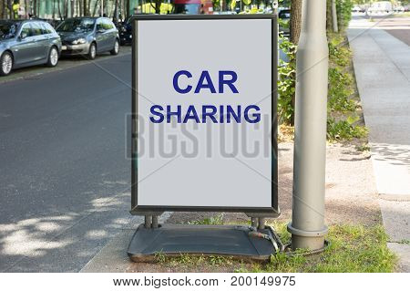 Car sharing sign on board by street in city