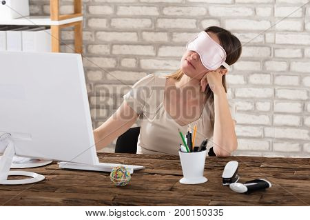 Close-up Of Young Woman With Pink Eye Mask Sleeping On Office Desk