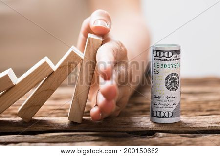 A Person Preventing Rolled Up Banknotes From Falling Wooden Blocks