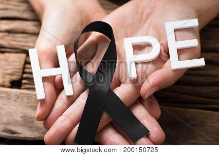 Person's Hand Showing Ribbon With Hope Text To Support Melanoma Skin Cancer Awareness