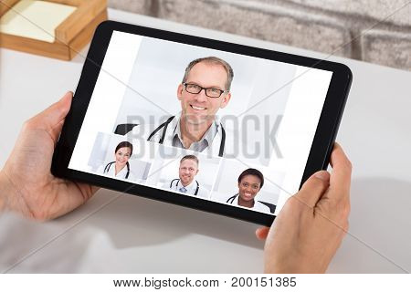 A Person Videoconferencing With Smiling Male And Female Doctors On Digital Tablet