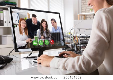 Close-up Of A Businesswoman Videoconferencing With Happy Male And Female Colleague On Computer