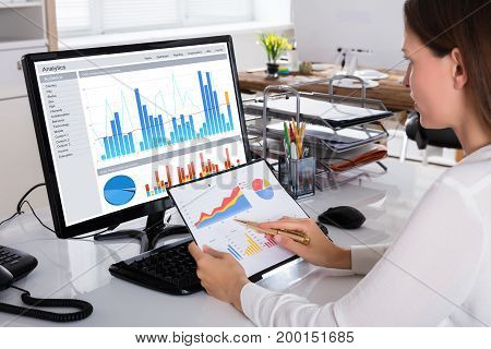 Close-up Of A Young Businesswoman Checking Graph On Computer In Office