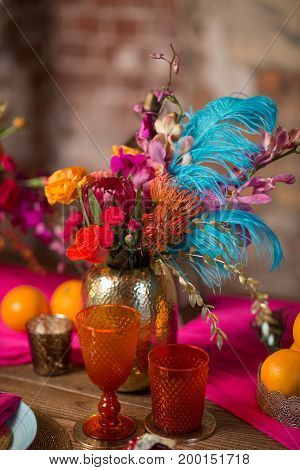 A table set with glass decorate in purple, orange and pink