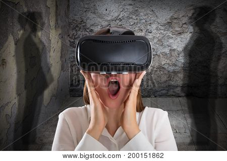 Close-up Of A Afraid Woman Wearing Virtual Reality Glasses With Mouth Open Near Shadowy Figure