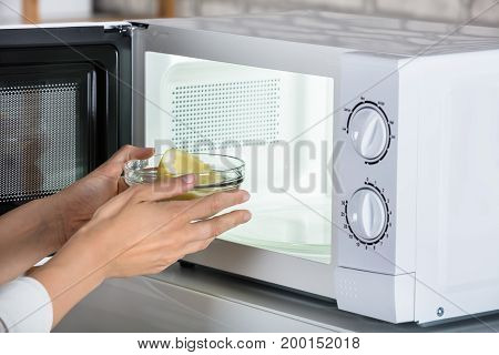 Close-up Of Woman Putting Bowl Of Slice Lemon In Microwave Oven