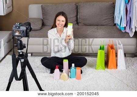 Happy Young Woman Holding Cosmetic Product For Blog At Home
