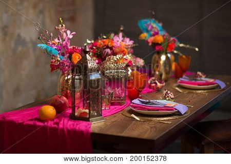 A table set vase with flowers, plates decorate in purple and pink colors