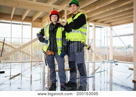 Confident Female Carpenter Standing By Colleague At Construction