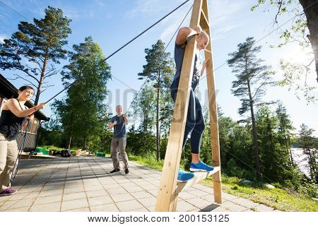 Male And Female Friends Pulling Ropes To Balance Woman On Wooden