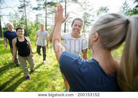 Women Giving High-Five While Friends Walking At Forest