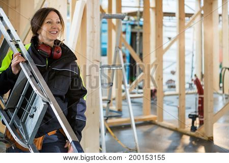 Female Carpenter Carrying Ladder At Construction Site