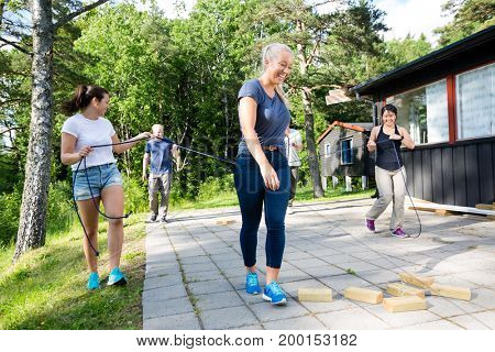 Friends Carrying Ropes While Walking Towards Wooden Blocks On Pa