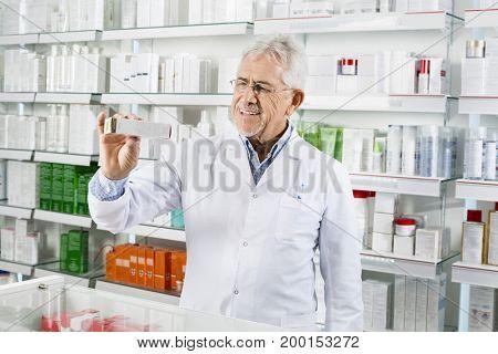 Senior Pharmacist Showing Medicine Box At Counter