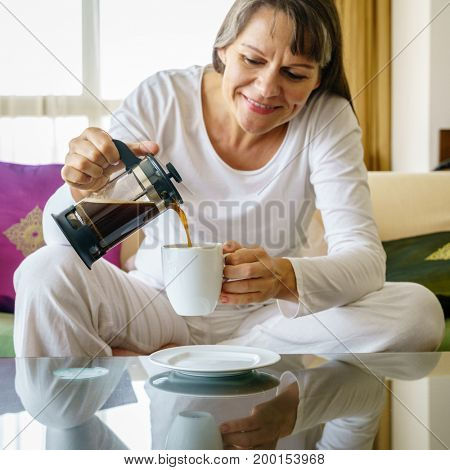 Mature woman is pouring fresh black coffee into a cup. Focus on the coffee pot
