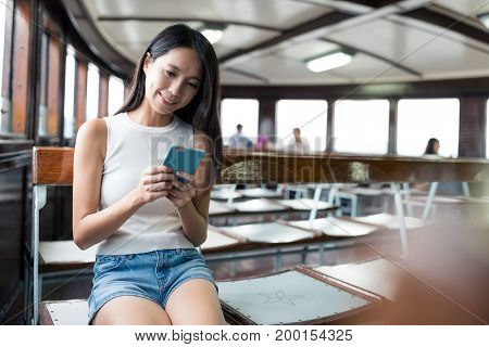 Woman look at the mobile phone and taking ferry in Hong Kong
