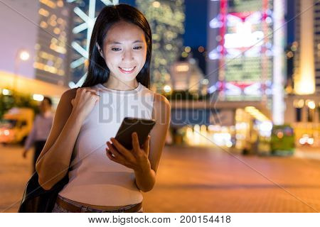 Woman holding with cellphone at night