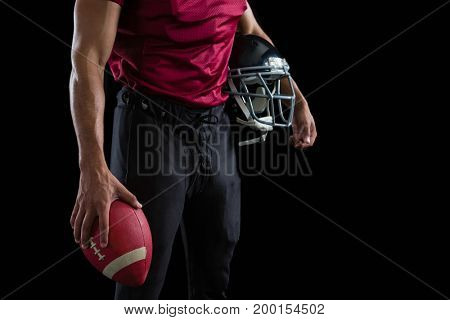Mid section of American football player holding a ball and head gear