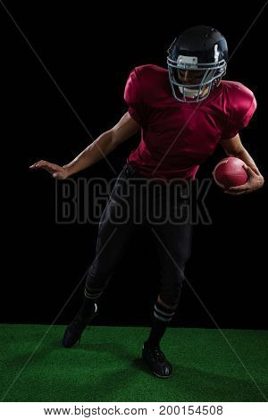 American football player leaning sideways with ball in one of his hand on artificial turf