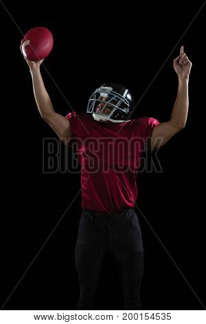 American football player raising hands holding a ball high in one hand against black background