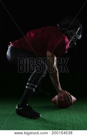 American football player bending holding a ball on turf with both his hands