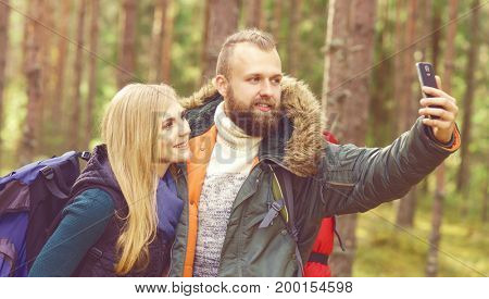 Young beautiful couple walking in forest and taking selfie on a smartphone. Camp, tourism, hiking concept.