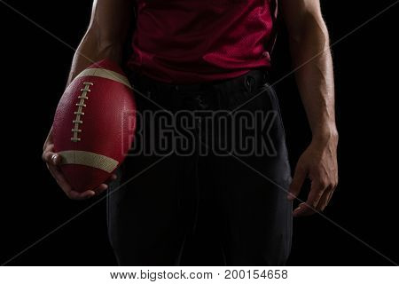 Mid section of American football player holding a ball in one hand
