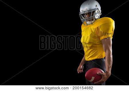 Portrait of American football player holding a ball against a black background